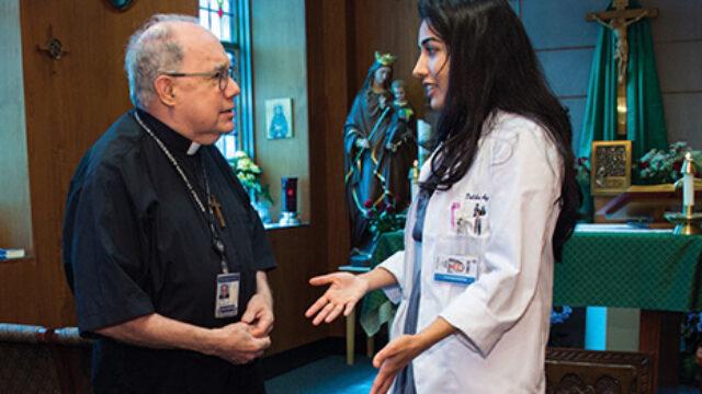 Daliha Aqbal speaks with Medical Center chaplain Fr. Sal Jordan, S.J. In the Med-Dent chapel.