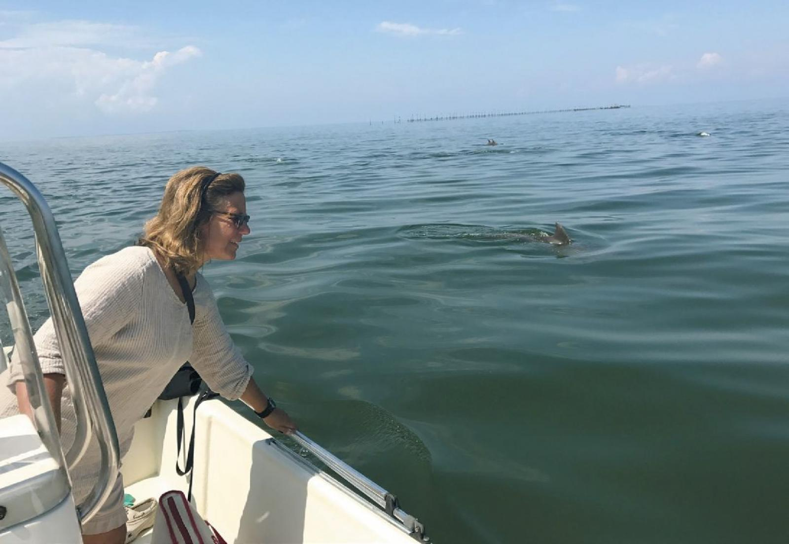 Professor Janet Mann looks off the side of Ahoya, the Potomac-Chesapeake Dolphin Project's boat, to observe a group of dolphins traveling through the Potomac.