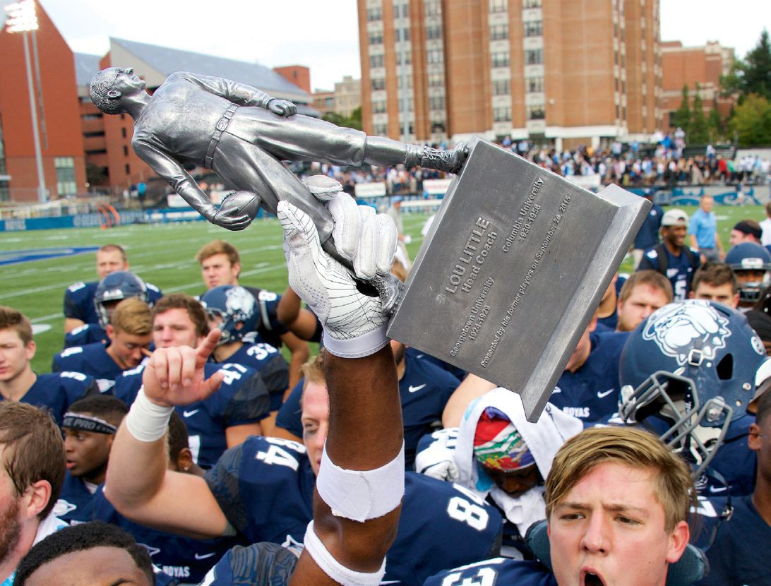 georgetown football players holding lou little trophy