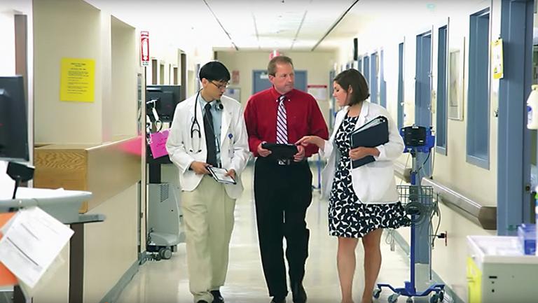 doctors talking as they walk down hospital hallway
