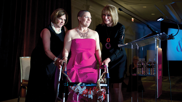 Event co-chairs Janet Davis (left) and Barbara McDuffie (right) help awardee Susan Miller to the podium.