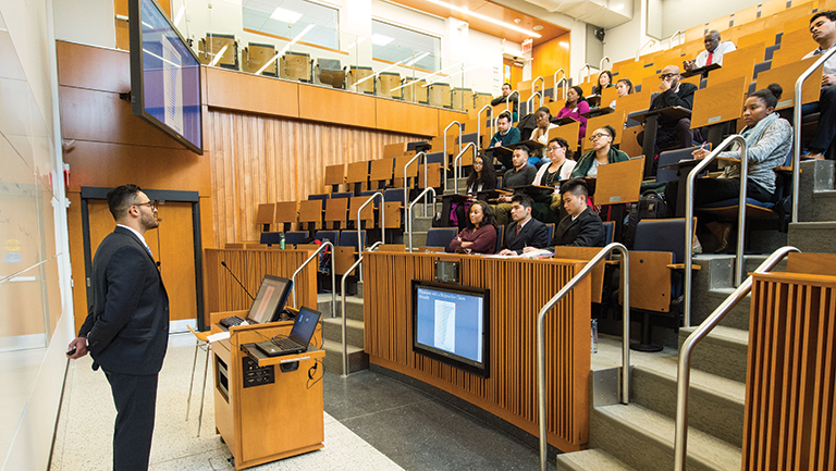students sitting in lecture hall with professor