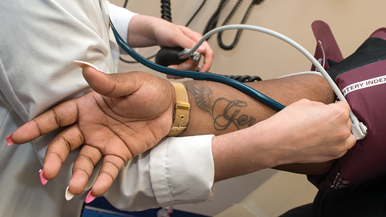 doctor putting stethoscope on patient's arm