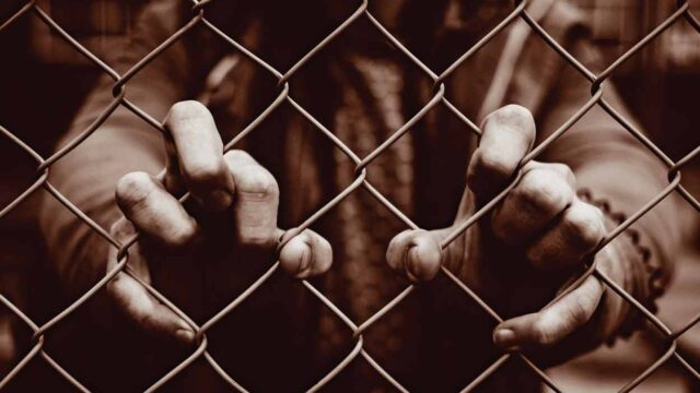 person putting fingers thru chainlink fence