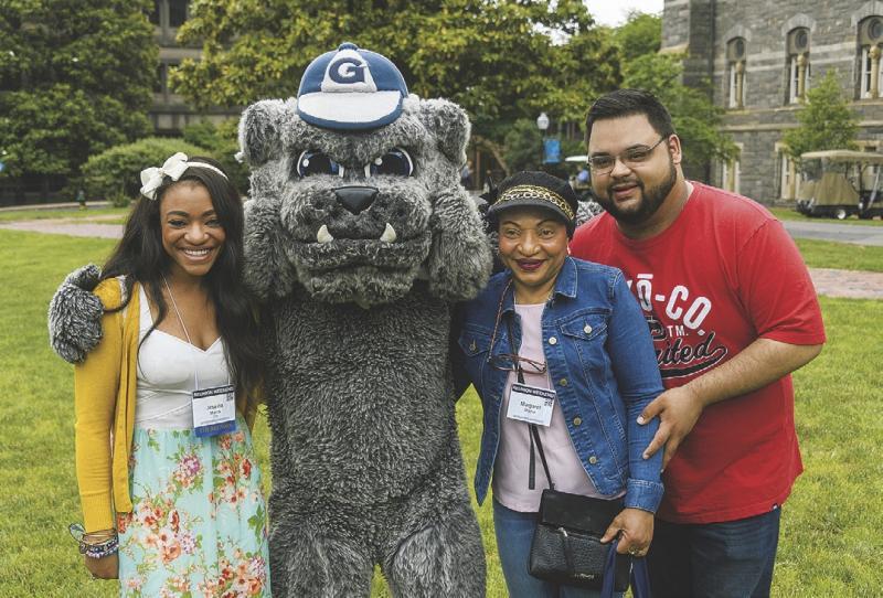 3 alumni posing with mascot