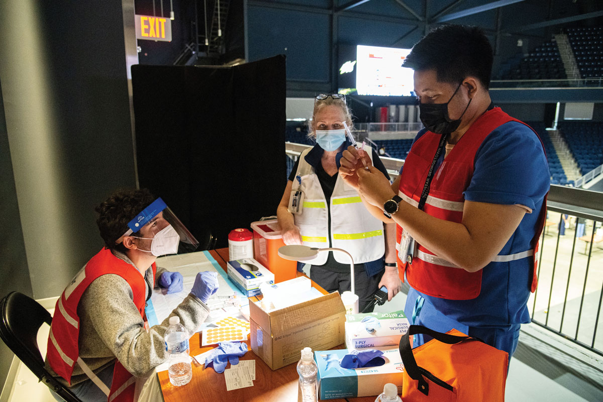 Dr. Ranit Mishori (center), medical director at the COVID-19 high-capacity vaccination site at D.C.'s Entertainment and Sports Arena, observes as Leon Padil- lia, nurse for MedStar Georgetown Student Health Center, instructs a medical student on how to prepare a dose of COVID-19 vaccine.